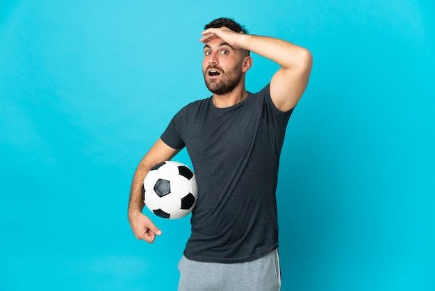 Футболист, изолированные на синем фоне, делает неожиданный жест, глядя в сторону