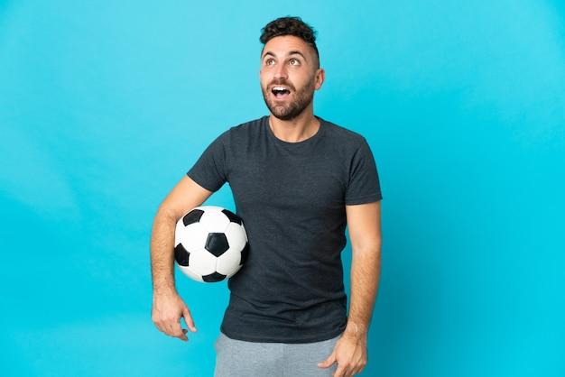 Футболист изолирован на синем фоне, глядя вверх и с удивленным выражением лица