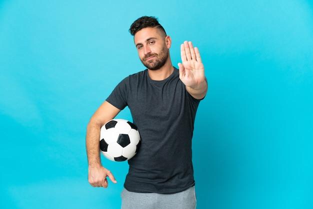 Футболист, изолированные на синем фоне, делая жест остановки