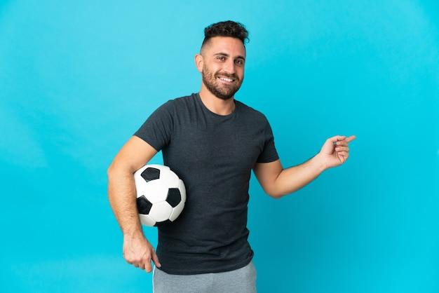 横に指を指している青い背景に分離されたサッカー選手
