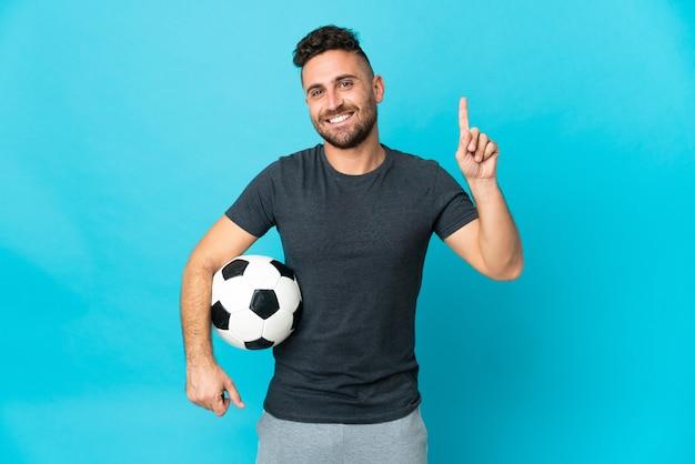 Футболист изолирован на синем фоне, указывая на отличную идею