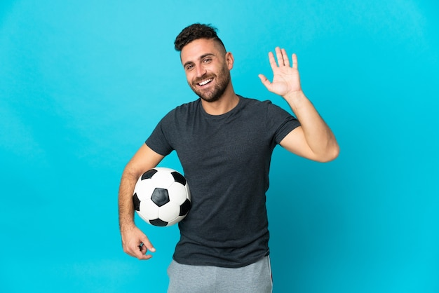 Футболист изолирован на синем фоне, салютуя рукой с счастливым выражением лица Premium Фотографии