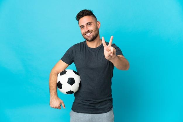 웃 고 승리 기호를 보여주는 파란색 배경에 고립 된 축구 선수