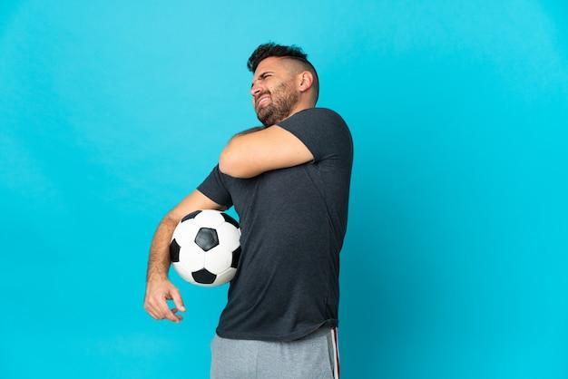 努力したために肩の痛みに苦しんでいる青い背景に孤立したサッカー選手