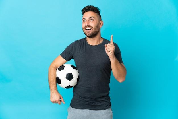 Футболист изолирован на синем фоне, думая об идее, указывая пальцем вверх