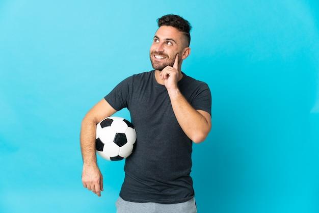 Футболист изолирован на синем фоне, думая об идее, глядя вверх