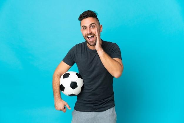 Футболист изолирован на синем фоне с удивленным и шокированным выражением лица