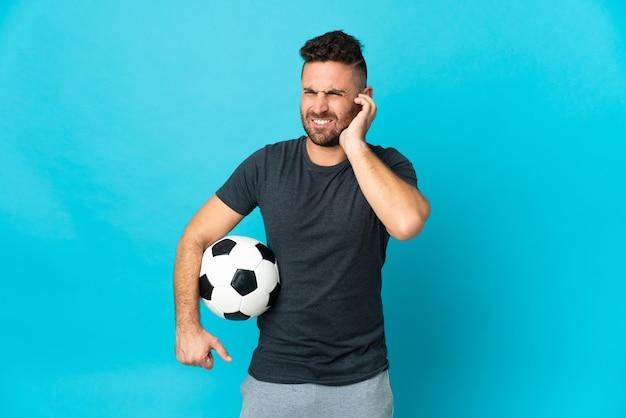 欲求不満と耳を覆っている青い壁に孤立したサッカー選手