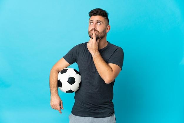 Футболист изолирован на синей стене с сомнениями, глядя вверх