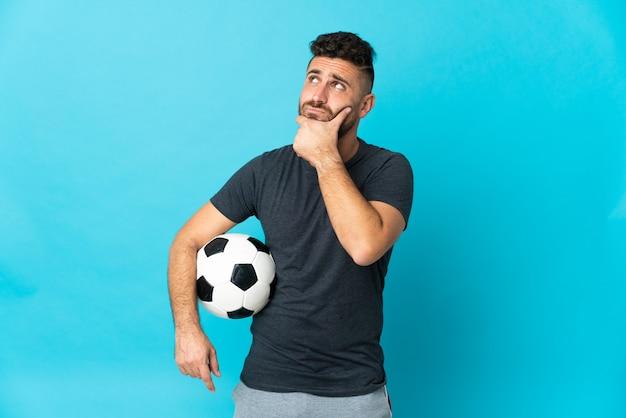 Футболист изолирован на синей стене, сомневаясь