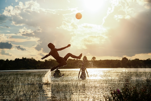 Football player kick soccer with sunset background