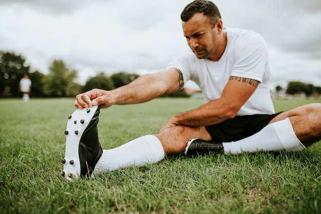 Football player stretching before a match