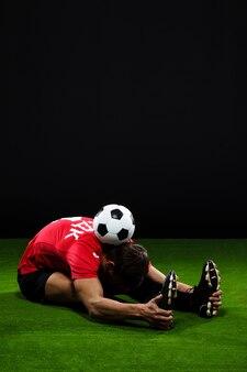 Футболист растягивается на траве с мячом
