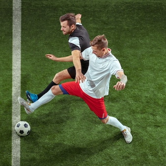Football player tackling for ball over green grass wall. professional male soccer players in motion at stadium. fit jumping men in action, jump, movement at game.