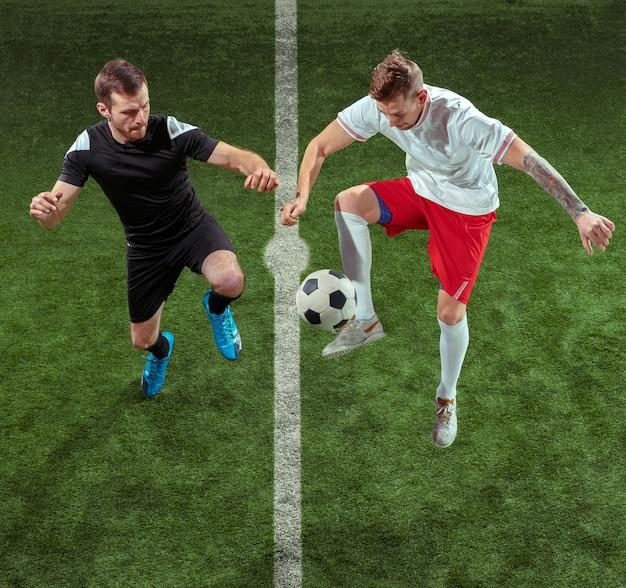 녹색 잔디 배경 위에 공에 대 한 태 클 축구 선수. 모션 경기장에서 프로 남성 축구 선수입니다. 게임에서 행동, 점프, 움직임에 점프하는 남자를 맞추십시오.