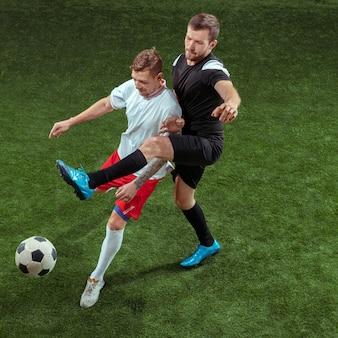 Футболист решает мяч на фоне зеленой травы. профессиональные футболисты мужского пола в движении на стадионе. приспособьте прыгающих мужчин в действии, прыжке, движении в игре.