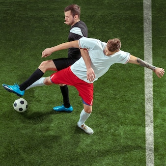 緑の芝生の背景の上にボールに取り組んでいるサッカー選手。