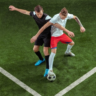 Футболист решает мяч на фоне зеленой травы.
