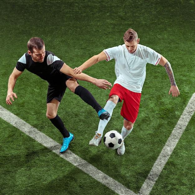 녹색 잔디 벽에 공을 위해 태 클하는 축구 선수. 모션 경기장에서 프로 남성 축구 선수입니다. 액션, 점프, 게임에서 점프하는 남자를 맞추십시오.