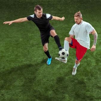 푸른 잔디 위에 공을 위해 태 클하는 축구 선수