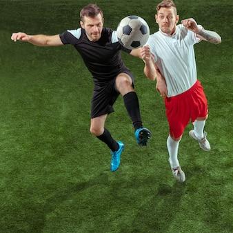 緑の芝生の上でボールに取り組むサッカー選手