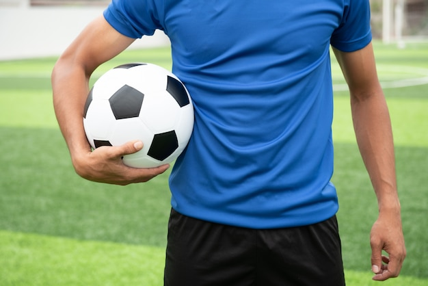 サッカー選手、黒のサッカーボールを持って、青いシャツを着て。