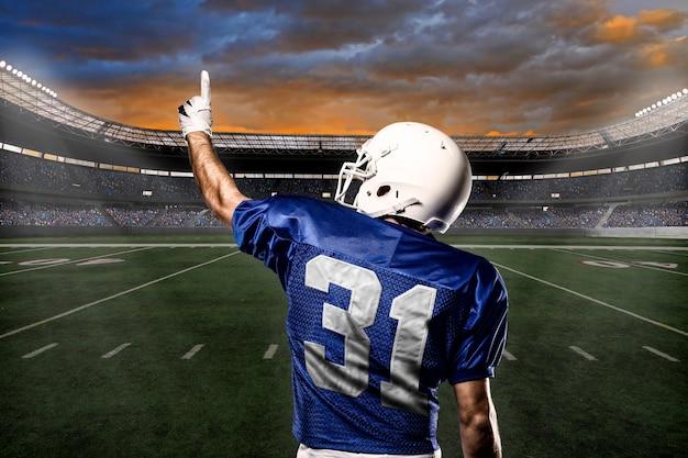 Футболист в синей форме празднует с болельщиками.