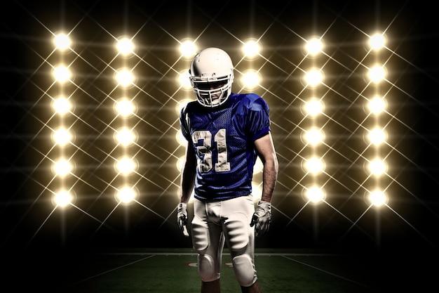 ライトの前に青いユニフォームを着たサッカー選手