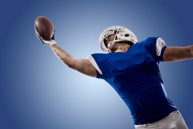 青い壁に引っ掛かる青いユニフォームを着たフットボール選手
