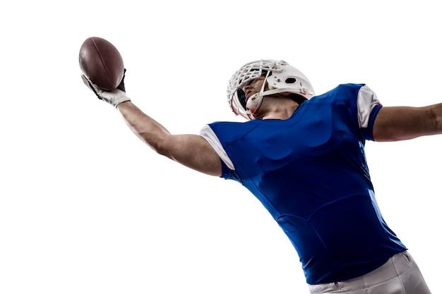 흰 벽에 잡기를 만드는 파란색 유니폼과 축구 선수