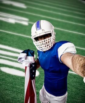 Футболист в синей форме делает селфи на футбольном поле