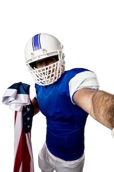 Футболист в синей форме делает селфи на белой стене