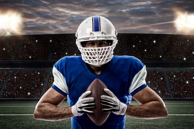 Футболист в синей форме на стадионе