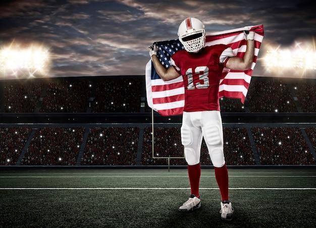 Футболист с красной формой и американским флагом на стадионе.