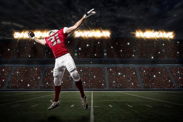 Футболист в красной форме ловит мяч на стадионе.