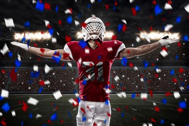 Футболист с красной формой празднует, на стадионе.