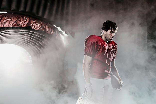 赤いユニフォームを身に着けているファンがいるスタジアムで赤いユニフォームを備えたフットボール選手