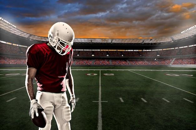 Футболист в красной форме на стадионе с болельщиками в красной форме