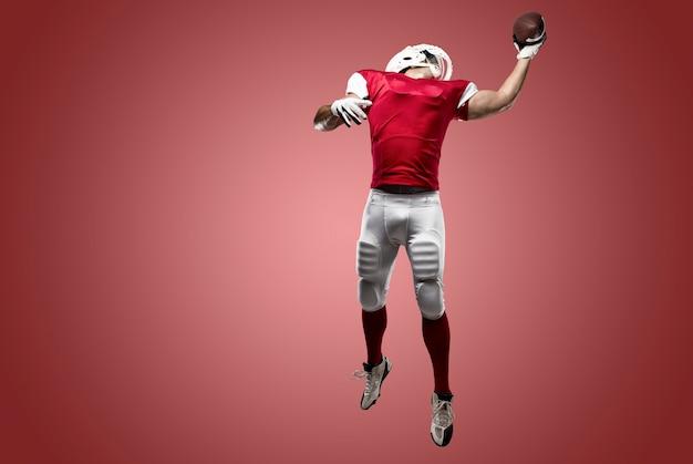 赤い壁に引っ掛かる赤いユニフォームを着たサッカー選手