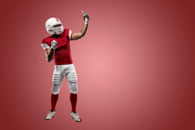 赤い壁に自分撮りをする赤い制服を着たサッカー選手