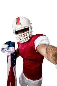 Футболист в красной форме делает селфи на белом