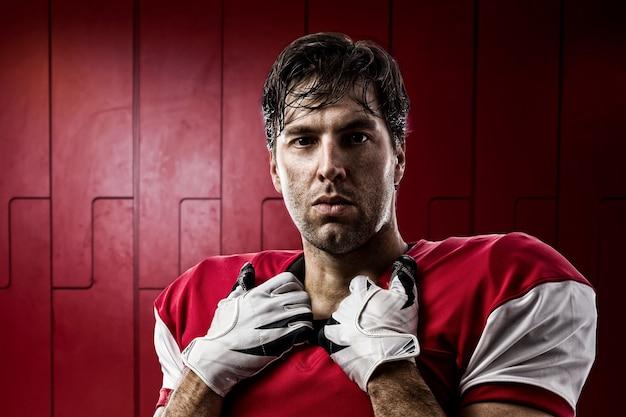 Футболист в красной форме на рундуке.