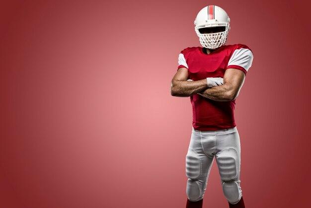 赤い壁に赤いユニフォームを着たサッカー選手