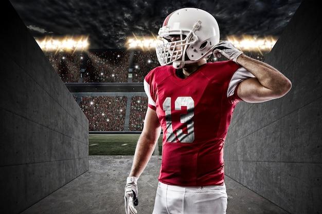 Футболист в красной форме на туннеле стадиона.