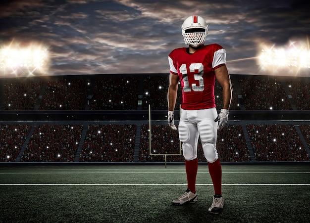 スタジアムで赤い制服を着たフットボール選手。