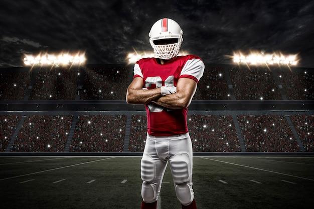 Футболист в красной форме на стадионе.