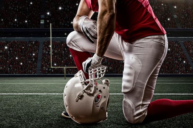 Футболист в красной форме на коленях на стадионе.