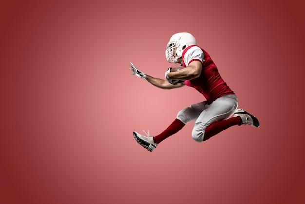 赤い制服を着たサッカー選手が赤い壁を走っている