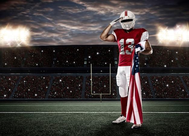 Футболист в красной форме салютует американским флагом на стадионе.