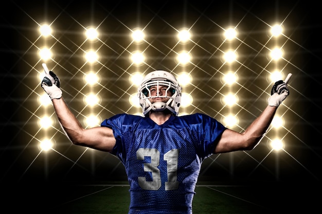 Football player with a blue uniform celebrating in front of lights